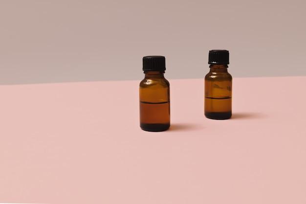 파스텔 핑크와 회색 배경에 미용 제품을 위한 두 개의 작은 갈색 유리 화장품 병. 복사 공간이 있는 최소 구성. 자기 관리 웰빙 개념입니다.