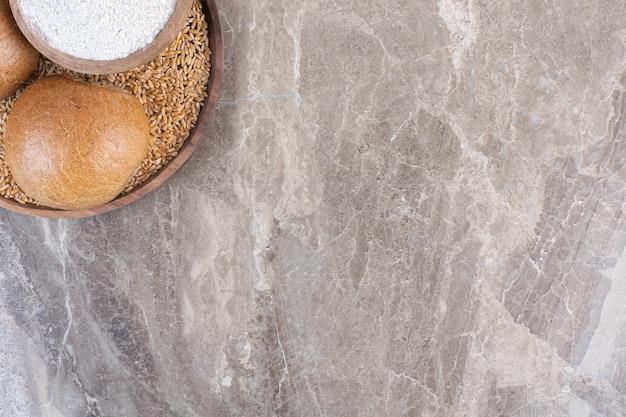 Due piccoli panini e una ciotola di farina su un vassoio in marmo.