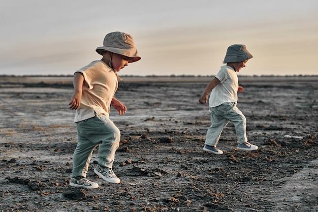 Двое маленьких детей идут по проселочной дороге