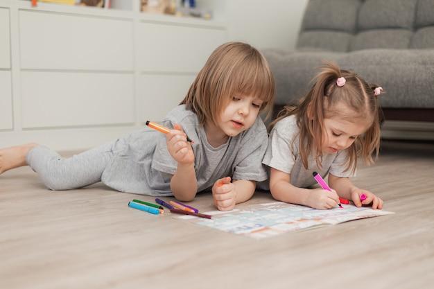 2人の小さな子供男の子と女の子が木の床に家で横になって絵を描きます。高品質の写真
