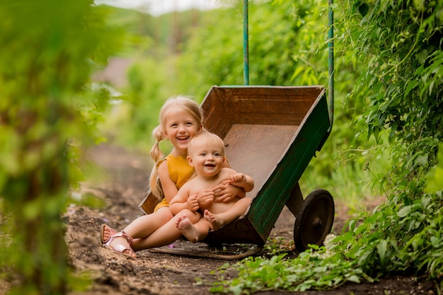 Two small children girl and boy in the country in a garden wheelbarrow sitting smiling