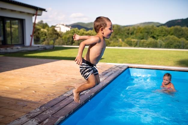 屋外のプールで遊んだりジャンプしたりする2人の小さな子供。