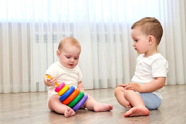 Двое маленьких детей с голубыми глазами играют в игровой комнате.