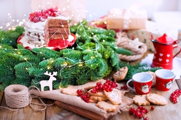 Two small cups of coffee and a coffee pot, a cake with berries and cookies, gifts, near a christmas tree on a village table near the window