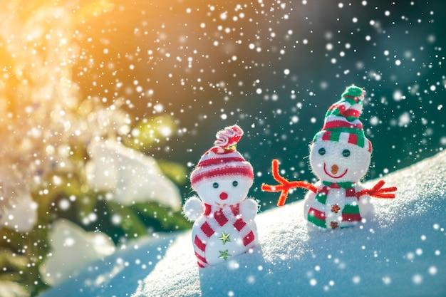 Два маленьких забавных игрушечных снеговика в вязаных шапках и шарфах в глубоком снегу на открытом воздухе возле сосновой ветки. поздравительная открытка с новым годом и рождеством.