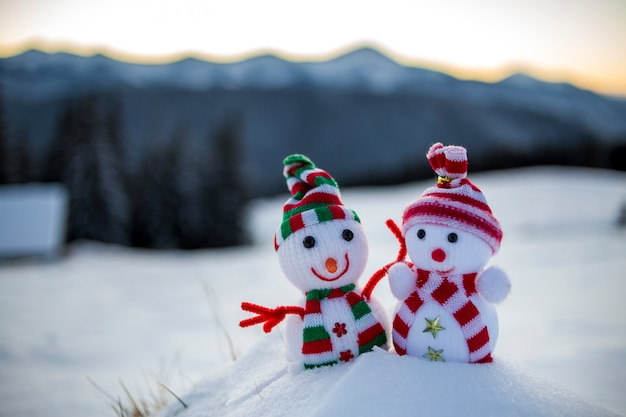 Two small funny toys baby snowman in knitted hats and scarves in deep snow outdoors