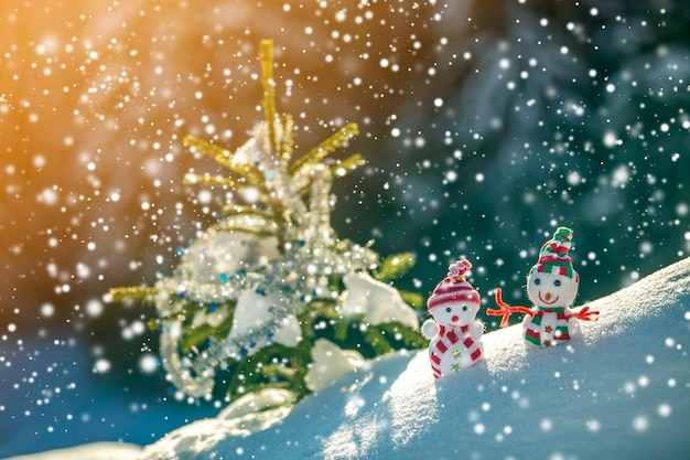 Two small funny toys baby snowman in knitted hats and scarves in deep snow