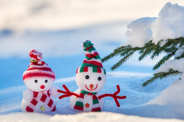 Two small funny toys baby snowmen in knitted hats and scarves in deep snow outdoors near pine tree branch