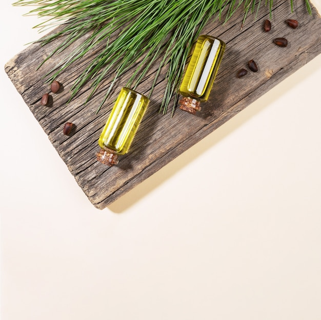 Two small glass bottles of essential cedar oil on old wooden board with cedar branch and nuts on beige backdrop with copy space. coniferous spa aromatherapy and spa products concept. square photo.