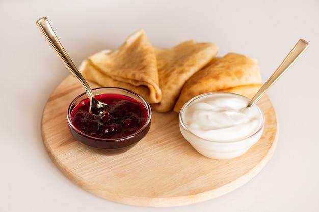 Две маленькие стеклянные миски с домашним вишневым джемом и сметанным кремом и три аппетитных горячих блина на деревянной доске