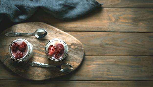 금속 숟가락으로 나무 스탠드에 딸기와 요구르트의 두 개의 작은 항아리. 평면도