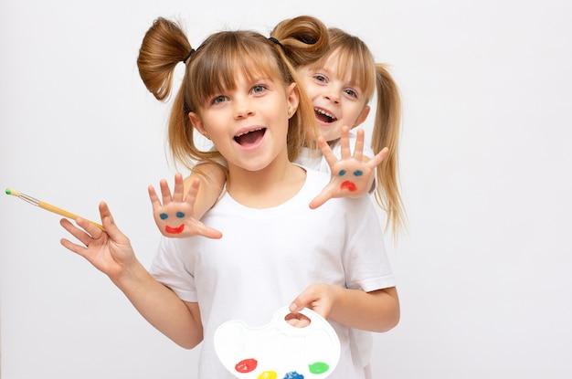 흰색 배경에 격리된 그녀의 손에 팔레트(수채화 물감)와 브러시가 있는 두 명의 작은 멋진 여자 예술가. 어린이 취미에 좋은 그림 - 2