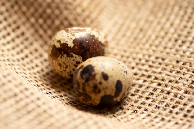 Два небольших перепелиных яйца на джутовой мешковине.