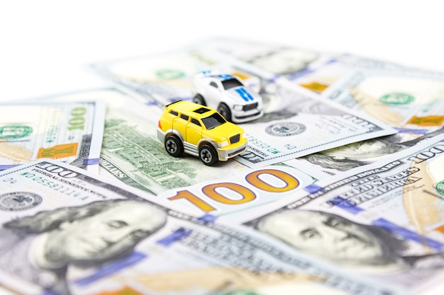 Two small toy cars on dollars. car purchase and insurance. car rental, repair, maintenance