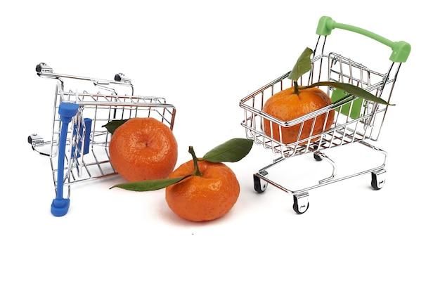 슈퍼마켓에서 식료품을 위한 작은 장난감 카트 2개와 흰색 배경에 분리된 녹색 잎이 있는 귤 3개.