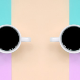 Two small white coffee cups on pink, blue, coral and lime colors paper