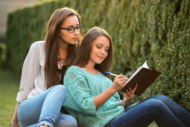 Two smart female students are sitting on grass at campus.