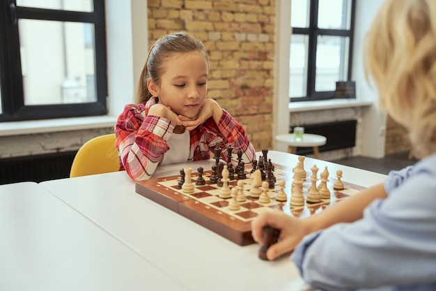 Two smart little children girl and boy playing chess while sitting at the table in school