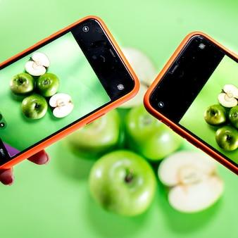 Два смартфона фотографируют зеленые яблоки на зеленом фоне