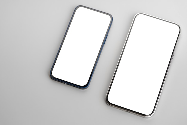 회색 표면에 빈 흰색 화면이 두 스마트 폰