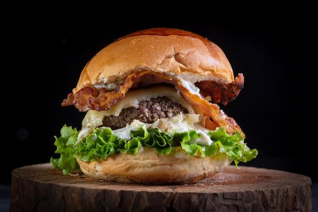 Два гамбургера с сыром, беконом, листьями салата и чесночным соусом