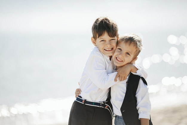 Two smiled brothers are hugging each other near the sea and looking straight