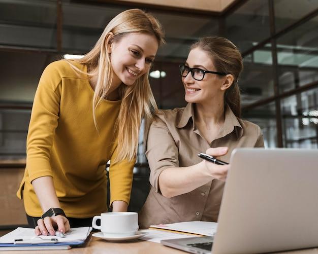 Две улыбающиеся женщины-предприниматели, работающие с ноутбуком за столом