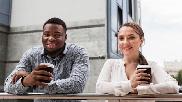Два улыбающихся коллеги вместе пьют кофе на работе во время пандемии