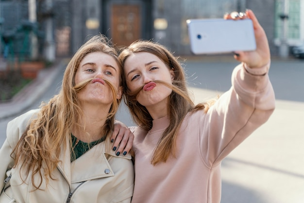 Two smiley female friends outdoors in the city taking a selfie