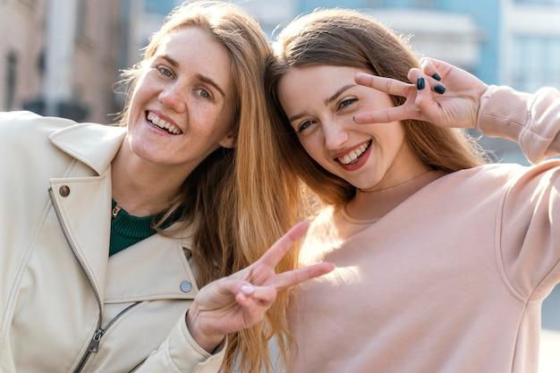 함께 포즈를 취하는 도시에서 야외에서 두 웃는 여자 친구