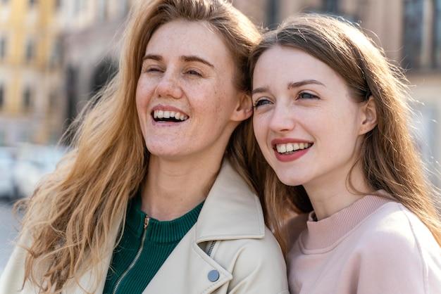 야외에서 도시에서 두 웃는 여자 친구
