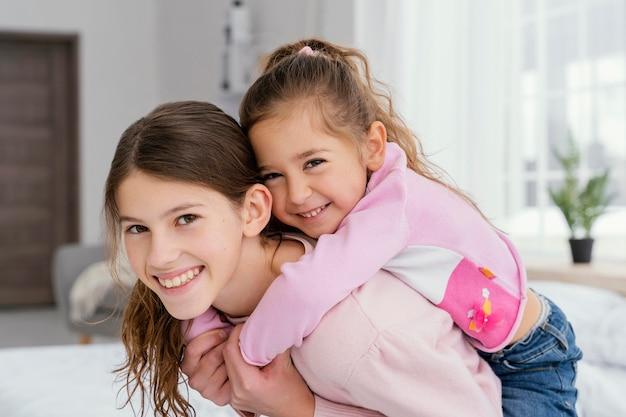 Две улыбающиеся сестренки вместе дома