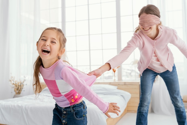 Two smiley sisters playing at home while blindfolded