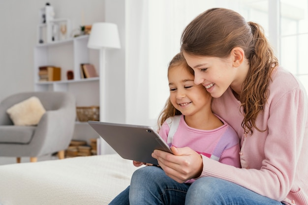 Two smiley sisters together at home using tablet