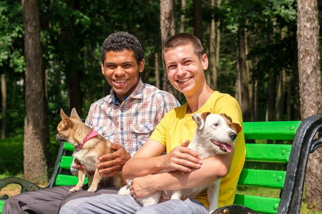 여름에 공원 벤치에서 개와 함께 웃고 있는 두 명의 아프리카계 미국인 및 백인 친구 프리미엄 사진