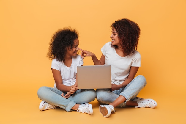 Two smiling afro american sisters holding laptop computer