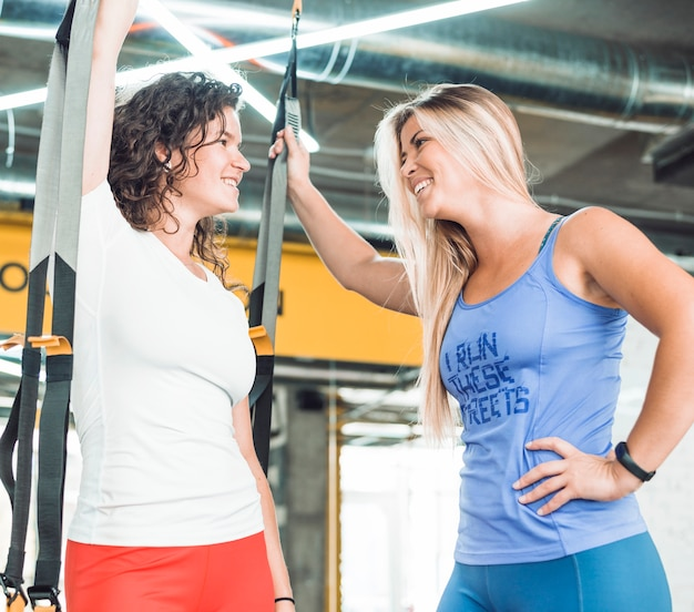 Two smiling athletic young women looking at each other in gym