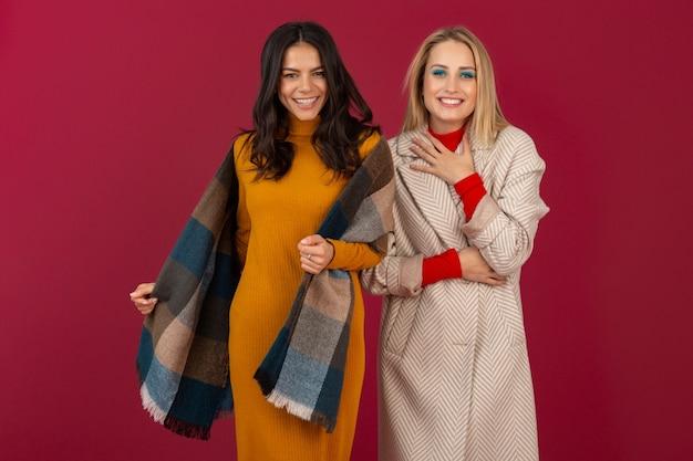 Due donne alla moda attraenti sorridenti in vestito da modo di autunno inverno e posa del cappotto isolata sulla parete rossa