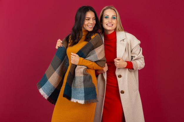 가을 겨울 패션 드레스와 코트에 두 웃는 매력적인 세련된 여성이 붉은 벽에 고립 된 포즈