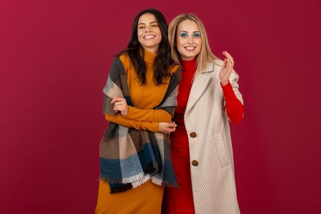 Две улыбающиеся привлекательные стильные женщины в осенне-зимнем модном платье и пальто позируют изолированно на красной стене
