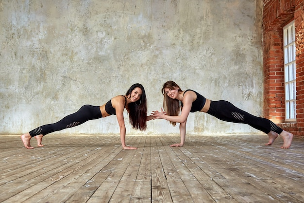 Two smiling beautiful, fitness girls doing exercises in the fitness room give five.