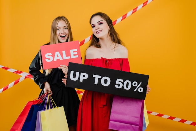 Two smiling beautiful girls have sale up to 50 sign with colorful shopping bags and signal tape isolated over yellow