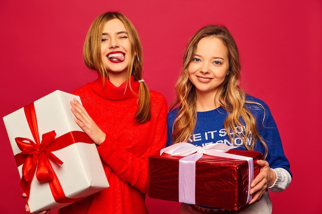 Two smiling beautiful women in stylish sweaters with big gift boxes