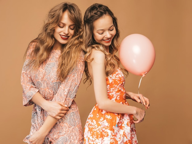 Two smiling beautiful women in summer dresses. girls posing.models with colorful balloons.having fun, ready for celebration birthday or holiday party