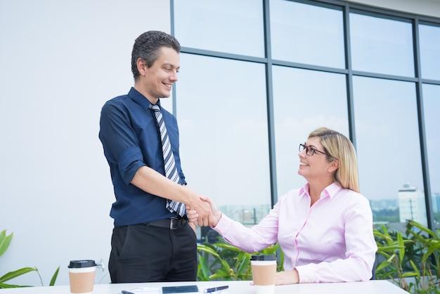 Два улыбающихся деловых партнеров рукопожатие в открытом кафе офиса.