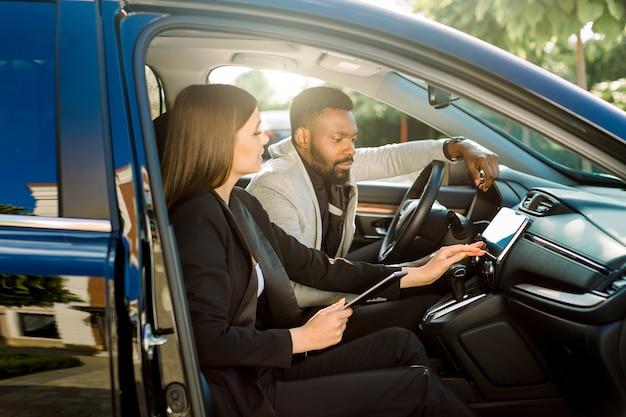 두 웃는 사업 사람들, 백인 여자와 아프리카 남자 차에 함께 앉아, 디지털 태블릿을 사용 하 고 작업. 회의로 운전하면서 비즈니스 전략에 대해 토론