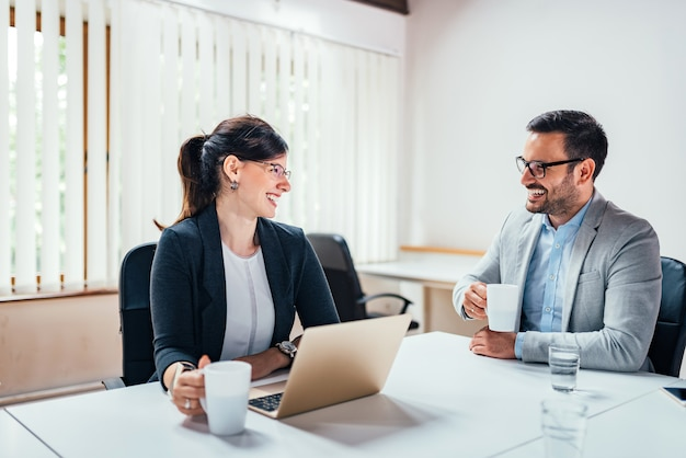 Two smiling business people drinking tea or coffee while sitting at office desk.