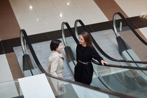 Two smiling business women standing on an escalator in a business center