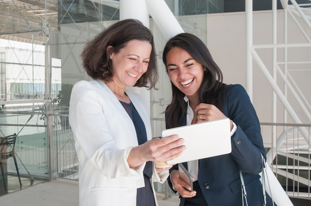 Two smiling business women using tablet in office hall