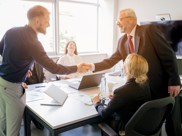 Two smiling businessman shaking hands together in the board meeting